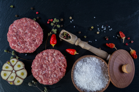 Fresh raw meat burger cutlet on the black slate board with herbs and spices for background. Copy space, top view.