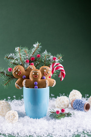 Christmas or new year card . Cup with fir trees, candy canes and ginger men cookies. On green bright background. 免版税图像
