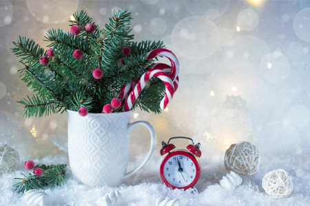 Christmas or new year card . Cup with fir trees, candy canes and red clock. On snow bright background.