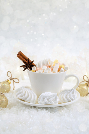 Blurred background of winter frost and Christmas chocolate spice beverage with sweets  in white cups