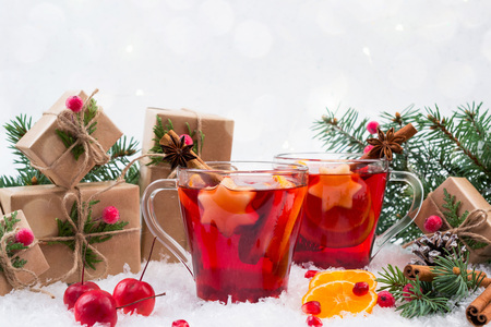 Traditional hot drink at Christmas time. Christmas mulled red wine with spices and fruits. On white snow background
