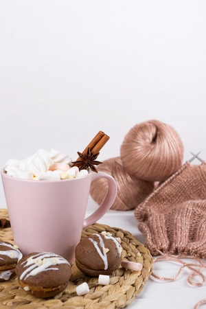 Cup of fresh coffee with marshmallow and knitted sweater from rose yarn on a white background Archivio Fotografico