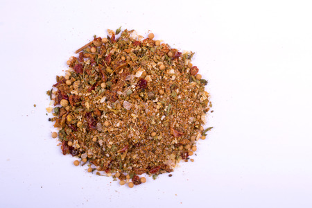 A pile of a red grill spice mix. Isolated on white background. Spices consist of paprika, pepper, coriander