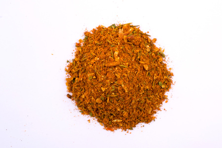 A pile of a yellow spice mix for chicken  . Isolated on white background. Spices consist paprika onion garlic mustard coriander thyme celery turmeric fennel black pepper