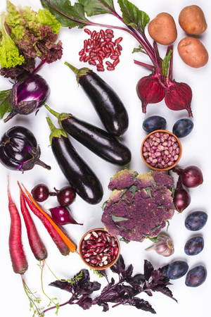 Assortment of fresh raw purple homegrown vegetables on white table. Cauliflower, eggplant, beets, carrots, potatoes, plums, basil, onions, garlic, beans, lettuce. Top view. Stockfoto