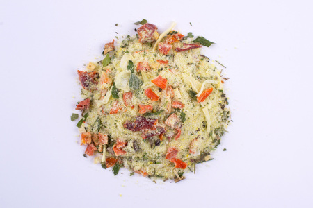 A pile of a yellow spice mix. Isolated on white background. Spices consist dried dehydrated  vegetables carrot paprika onion garlic parsnip parsley tomatoes