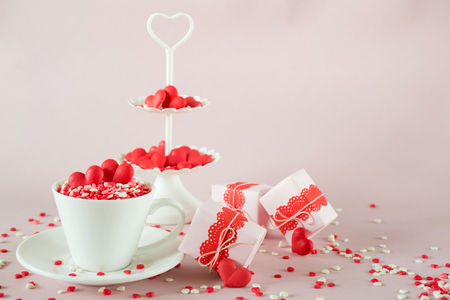 Festive background.  Coffee cup, white two tier serving tray full of multicolor sweet sprinkles sugar candy hearts and packing Valentines  Day gifts  Love and Valentines day concept.