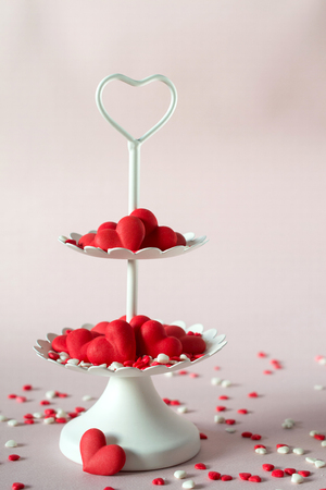 White two tier serving tray full of multicolor sweet sprinkles sugar candy hearts.  Love and Valentines day concept. Stock Photo