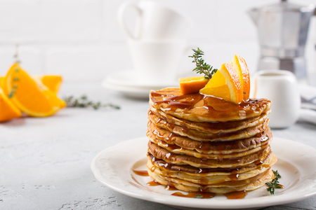 Pancakes with orange and sprinkled maple syrup, orange juice and coffee Фото со стока - 95244369
