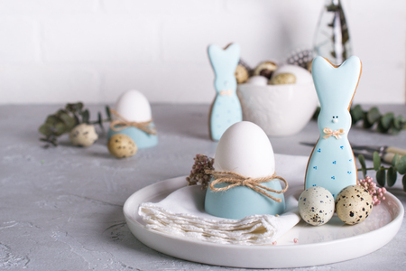 Homemade easter cookies in the shape of  a  funny  bunny, quail eggs  and chicken egg. Easter  celebration table setting. Holiday decorations. Stock Photo