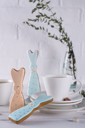 Easter bunny cookies and cup of tea. Celebration breakfast table setting. Holiday decorations.