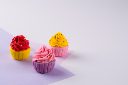 Decorative  multicolored sugar  cupcakes on light  background with sprinkles