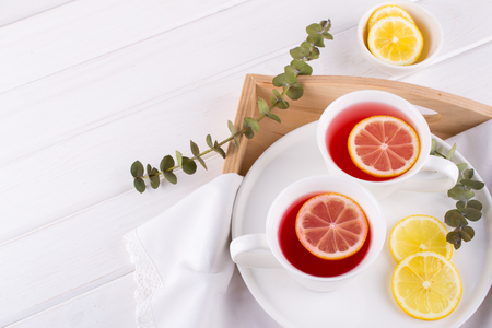 Two cups of red fruit and herbal tea with lemon slice, top view Фото со стока
