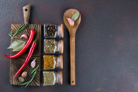 Group of spices and herbs  on dark background with top view and copy space for design