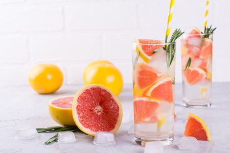 Mineral infused water with grapefruit ice, and rosemary on white background, homemade detox soda water recipe.