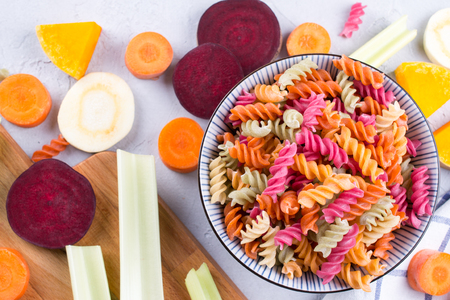 Background of bright colorful dry pasta made from vegetables and its natural vegetable dyes celery, beet, carrot, pumpkin, parsnip. Healthy food concept