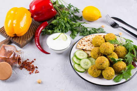 Homemade spicy chickpea falafel garnished with fresh vegetable and yogurt on a plate over light concrete background. Israeli cuisine concept Stock Photo