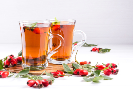 Healthy autumn  tea with dog roses, branch with berries on white  background. Standard-Bild