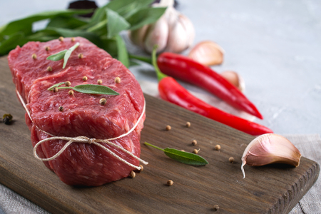 Raw beef steak with ingredients for cooking on cutting board . Stock Photo