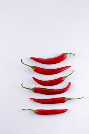 Pods of  red hot chili peppers on white background Stock Photo