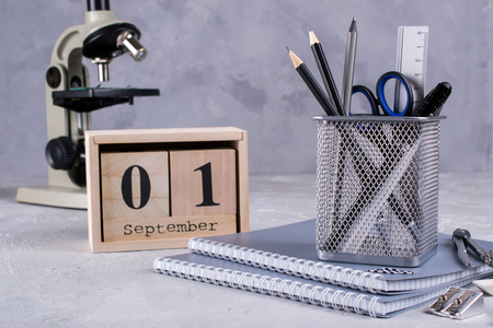 1st September. Wooden calendar, group of school supplies  on a gray table. Back to school concept. Stock Photo