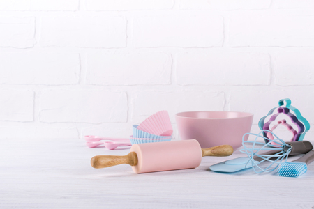 Sfondo di cottura con utensili da cucina: mattarello, cucchiai di legno, frusta, setaccio, bakeware e tagliabiscotti di forma su fondo di legno bianco. Archivio Fotografico