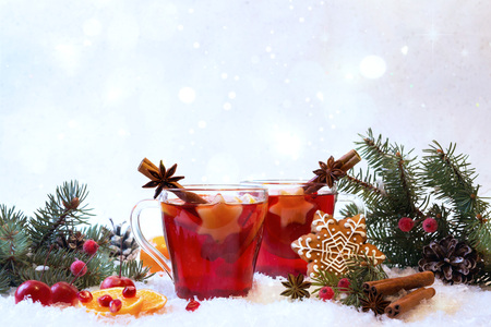 Hot mulled spiced red wine in glass mug with with festive decoration lights and gingerbread . On white snow background