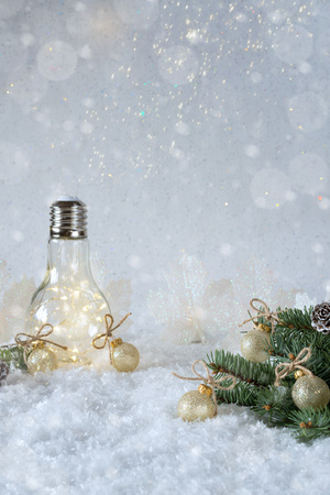 New Years decoration. Christmas tree branch with balls on snow background and beautiful lamp light. Copy space