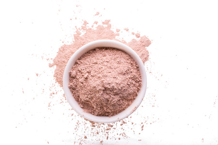 Dry pink clay powder mask for face and body  in ceramic bowl isolated on white Stock Photo