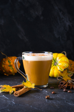 Pumpkin spiced latte or coffee in glass cup, dry leaves. Traditional autumn or winter hot drink. Space for text