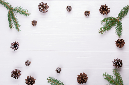 Christmas frame made fir tree branches, and pine cones decoration rustic elements on white wood table. Banco de Imagens