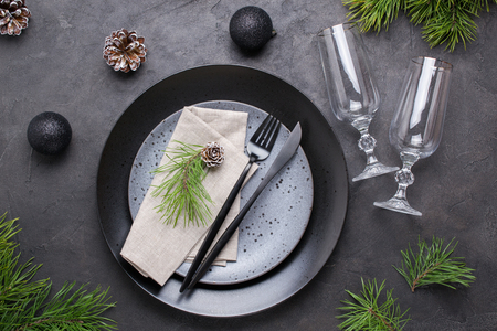 Dark christmas table setting design. Black  plates, champagne glasses, fork and knife set with napkin, fir branch, christmas decorations
