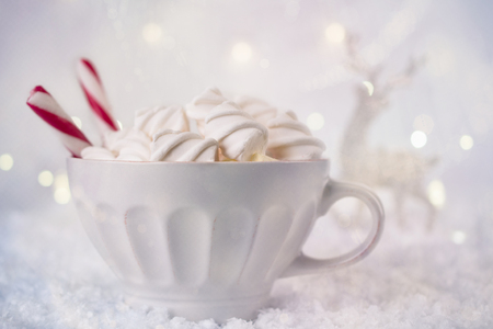 Hot Coffee cup with marshmallows and red candy cane on a frosty winter background. Christmas holidays background. Copy space for text. Stock Photo