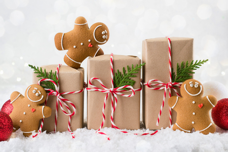 Packing Christmas gifts.  Three Christmas gift boxes wrapped in kraft paper tied with red and white string and three smiling  gingerbread men cookies on white winter background. copy space Foto de archivo