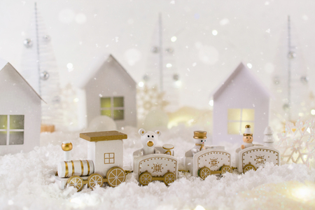 Frosty winter wonderland with toy train, snowfall and magic lights.  Christmas greetings concept, greeting card