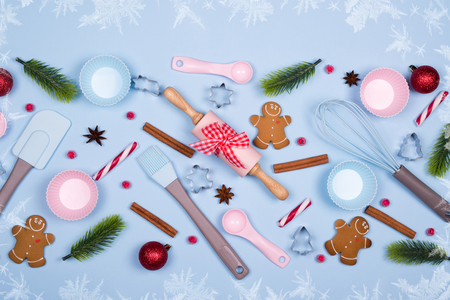 Christmas Baking background. Ingredients for cooking christmas cookies, kitchen utensils, gingerbread cookies on blue pastel background. Christmas decorative border made of festive elements Top view with copy space.