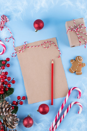Craft paper card and decoration on blue table top view. Christmas mockup for greeting, plans, wishes, goals. Flat lay. Merry Chraistmas and happy new year 2019