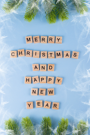 Merry Christmas and happy new year. Words from wooden letters on winter blue  background. Template, greeting card. Holiday concept.
