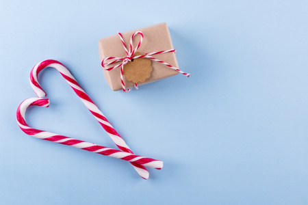 Present from secret Santa. Wrapped gift box with notes,  candy cane on blue pastel background. Top view, copy space