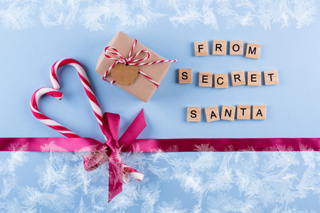 Present from secret Santa. Wrapped gift box with notes, candy cane and Pink , rose  ribbon with bow on blue pastel background. Top view, copy space. Simple festive design. Mockup