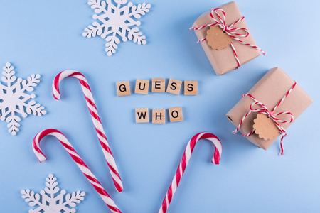 Secret Santa christmas game. Gift exchange. Wrapped gift boxes with notes candy cane on blue pastel background top view copyspace. Text from letters Guess whoa€| Stock Photo