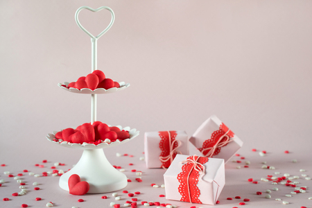 Valentines day concept. White two tier serving tray full of multicolor sweet sprinkles sugar candy hearts and packing Valentines  Day gifts Stock Photo