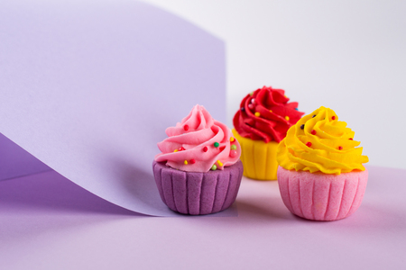 Decorative  multicolored sugar  cupcakes on light purple background with sprinkles