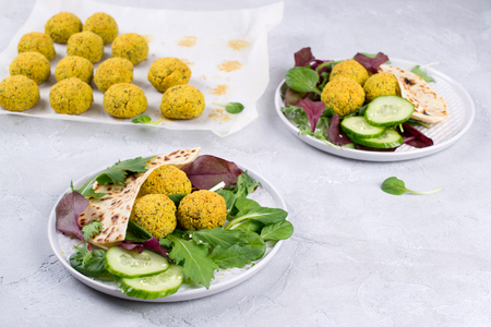 Plate of baked falafel with pita bread, tzatziki sauce and salad leaves on a table Banco de Imagens