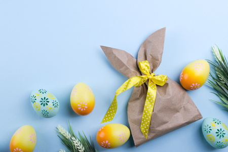 Easter composition with craft paper package in the shape of bunny, colorful easter eggs, and flowers. Flat lay, top view, copy space  Stock Photo