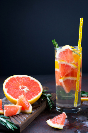 Mineral infused water with grapefruit ice, and rosemary on dark background, homemade detox soda water recipe.
