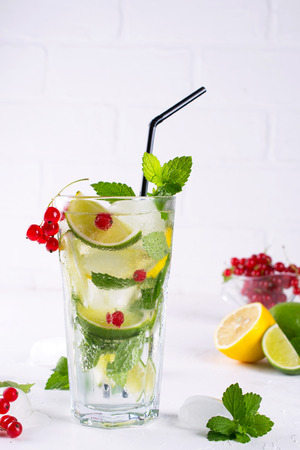 Various berry lemonade or mojito cocktails, fresh iced lemon lime , Red currant infused water, summer healthy detox drinks light background 스톡 콘텐츠