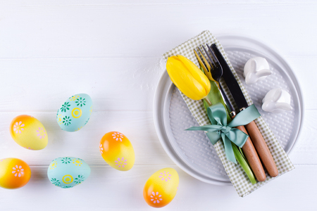 Spring Easter background for menu. Easter egg decoration, bunny, linen  napkin on plate and  kitchen cutlery on white wooden table. Flat lay