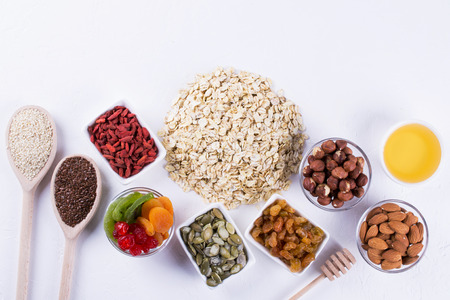 Ingredients for homemade oatmeal granola. Oat flakes, honey, nuts, dried fruit and seeds. Healthy breakfast concept.