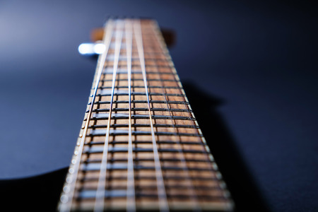 Electric guitar macro shot of a fretboard.Soft selective focus. On black background
